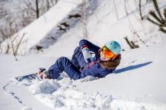 Foto von der Rückseite des Athleten im Sturzhelm, der auf schneebedeckter Steigung liegt Lizenzfreie Stockfotos