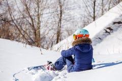 Foto von der Rückseite des Athleten im Sturzhelm, der auf schneebedeckter Steigung sitzt Lizenzfreies Stockfoto