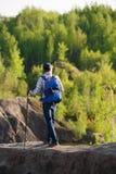 Foto von der Rückseite des jungen Touristen mit Spazierstöcken auf Hügel auf Hintergrund der Vegetation Lizenzfreie Stockbilder
