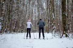 Foto von der Rückseite des Sports Frau und vom Mannskifahren im Winterwald Stockbild