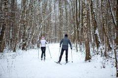 Foto von der Rückseite des Sports Frau und vom Mannskifahren im Winterwald Lizenzfreie Stockfotografie