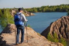 Foto von der Rückseite des touristischen Mannes in der Kappe mit Spazierstöcken auf Gebirgshügel nahe See lizenzfreies stockfoto