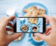 Foto von einem ` s machend, frühstücken Sie mit Schale coffe durch Smartphone Lizenzfreies Stockfoto
