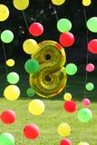 Foto von Feiertagsdekorationen von den Ballonen und vom Gold Abbildung 8 (acht) gegen den grünen Rasen und den dunklen Wald Stockfotografie