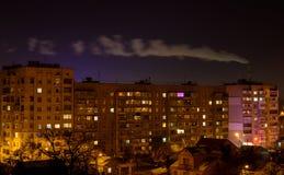 Foto von Gebäuden nachts mit Fabrikrauche über ihnen Lizenzfreie Stockbilder