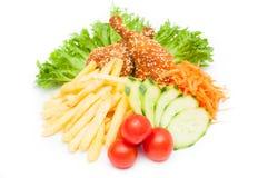 Foto von geschmackvollen Hühnernuggets mit Gemüse und gebratenem potatoe Lizenzfreies Stockfoto