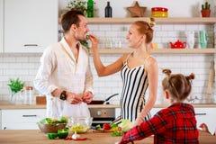 Foto von glücklichen Eltern und von Töchtern an einem Tisch mit Gemüse Stockfotografie