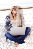 Foto von jungen Blondinen der Schönheit mit blauen Augen sitzt auf Bett wi Lizenzfreies Stockbild