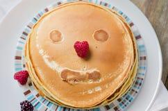 Foto von köstlichen Pfannkuchen mit Beeren und Honig über hölzernem t Lizenzfreie Stockbilder