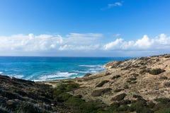 Foto von Meer, von bewölktem Himmel und von hügeliger Steigung Stockbilder