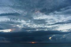 Foto von Meer, rote Sonne, bewölkter Himmel Lizenzfreies Stockbild