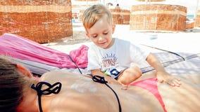 Foto von netten 3 Jahren alten kleinen Jungen, die der jungen Mutter Massage sich entspannt auf dem Sonnenbett am Seestrand mache lizenzfreie stockbilder