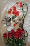 Foto von roten Rosen, von Rosenblättern und von Perlen Stockfoto