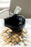 Foto von Sparschwein auf Stapel des Geldes mit Dollar im Schlitz Lizenzfreie Stockfotos