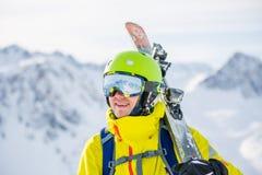 Foto von tragenden tragenden Gläsern des Sturzhelms des Mannes mit Skis Lizenzfreie Stockbilder