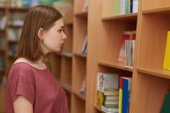 Foto von weiblichen Knabenhaltungen in der Buchhandlung, wählt was, für das Ablesen zu kaufen, betrachtet aufmerksam Titeln, hat  lizenzfreie stockfotos