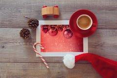 Foto von Weihnachtsfeiertagsdekorationen auf Holztisch mit Kaffeetasse und Sankt-Hut Ansicht von oben Stockbilder