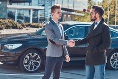 Foto von zwei intelligenten eleganten M?nnern, die ein Abkommen ?ber Auto haben stockbilder