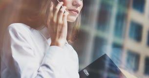 Fotoaffärskvinna som bär den moderna dräkten, den talande smartphonen och innehavdokument i händer Öppet utrymmevindkontor Royaltyfri Fotografi