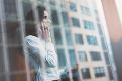 Fotoaffärskvinna som bär den moderna dräkten, den talande smartphonen och innehavlegitimationshandlingar i händer Öppet utrymmevi arkivbilder