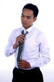 Fotobeeld die van een knappe aantrekkelijke jonge Aziatische zakenmanvulling, zijn band bevestigen en klaar te werken Royalty-vrije Stock Fotografie