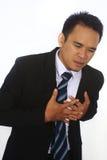 Fotobeeld van een knappe aantrekkelijke jonge Aziatische Zakenman die zijn hart in pijn houden Royalty-vrije Stock Afbeeldingen