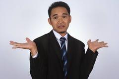 Fotobeeld van een knappe aantrekkelijke jonge Aziatische zakenman met trek ik ` t ken aan gebaar Royalty-vrije Stock Afbeeldingen