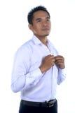 Fotobeeld van een knappe aantrekkelijke jonge Aziatische zakenmanvulling, knoop omhoog zijn overhemd Royalty-vrije Stock Foto's