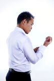 Fotobeeld van een knappe aantrekkelijke jonge Aziatische zakenmanvulling, knoop omhoog zijn overhemdskoker Royalty-vrije Stock Fotografie