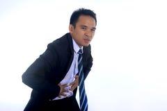 Fotobeeld van een knappe Aziatische zakenman die aan buikpijn lijden Stock Fotografie