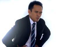 Fotobeeld van een knappe Aziatische zakenman die aan buikpijn lijden Stock Foto's