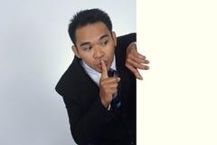 Fotobeeld van jonge Aziatische zakenman die een leeg teken met stil gebaar houden Stock Afbeelding