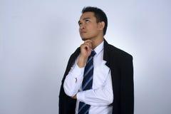 Fotobild av den tänkande gesten för ung asiatisk affärsman med det svarta dräktomslaget på hans skuldra Arkivfoto