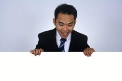 Fotobild av den unga asiatiska affärsmannen som rymmer ett tomt tecken Arkivfoton