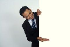 Fotobild av den unga asiatiska affärsmannen som rymmer ett tomt tecken med visninggest Royaltyfria Bilder