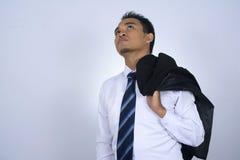 Fotobild av den unga asiatiska affärsmannen som rymmer hans dräktomslag på hans skuldra medan blick upptill som isoleras på vit Arkivbild