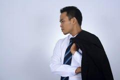 Fotobild av den unga asiatiska affärsmannen som rymmer hans dräktomslag på hans skuldra som isoleras på vit Royaltyfri Fotografi