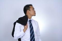 Fotobild av den unga asiatiska affärsmannen som rymmer hans dräktomslag på hans skuldra som isoleras på vit Royaltyfria Foton