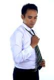 Fotobild av en stilig attraktiv ung asiatisk affärsmandressing, fixande hans band Arkivbild
