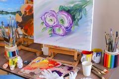 Fotobild som målas av konstnären och ställningar på staffli i konstdubb arkivbild