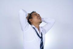 Fotobilden av den unga affärsmannen för den unga asiatiska affärsmannen frustated att tänka som isolerades på vit Arkivfoto