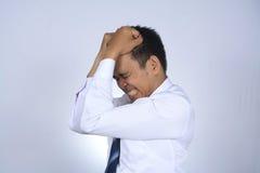 Fotobilden av den unga affärsmannen för den unga asiatiska affärsmannen frustated att tänka som isolerades på vit Arkivfoton