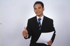 Fotobilden av en stilig attraktiv ung asiatisk affärsman med tummen räcker upp Arkivbild