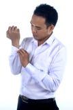 Fotobilden av en stilig attraktiv ung asiatisk affärsmandressing, knäppas upp hans skjortamuff Arkivbilder
