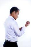 Fotobilden av en stilig attraktiv ung asiatisk affärsmandressing, knäppas upp hans skjortamuff Royaltyfri Fotografi