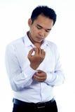 Fotobilden av en stilig attraktiv ung asiatisk affärsmandressing, knäppas upp hans skjortamuff Royaltyfri Bild