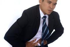Fotobilden av ett stiligt asiatiskt affärsmanlidande från buk- smärtar Royaltyfri Bild