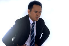 Fotobilden av ett stiligt asiatiskt affärsmanlidande från buk- smärtar Arkivfoton