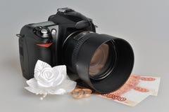 Fotocamera, huwelijk boutonniere, ringen met geld op grijs stock afbeeldingen