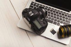 Fotocamera, lens en geheugenkaart op computer royalty-vrije stock afbeeldingen